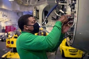 Aviation Structural Mechanic 2nd Class Christopher Mayweather maintains aircraft aboard USS Carl Vinson (CVN 70).