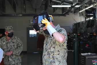 PORT HUENEME, Calif. (Aug. 26, 2021) Steelworker 1st Class Andrew Hagemeier teaches Rear Adm. Peter Garvin to weld like a Seabee during a steelworker schoolhouse tour at Naval Construction Training Center (NCTC) Port Hueneme.   NCTC Port Hueneme is one of five learning sites in the Center for Seabees and Facilities Engineering domain.  They train and develop Sailors, Soldiers, Airmen, and Marines in construction trades to accomplish contingency and peacetime construction, chemical, biological, and radiological operations, and humanitarian assistance missions worldwide. (U.S. Navy photo by Amber Vaglica)