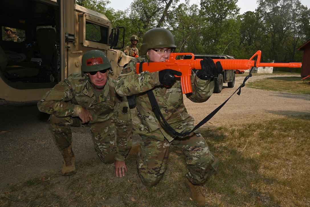 An enlisted religious affairs specialist practices defending his chaplain during a simulated enemy attack while conducting military training at Camp Grafton Training Center, N.D., Aug. 3, 2021.