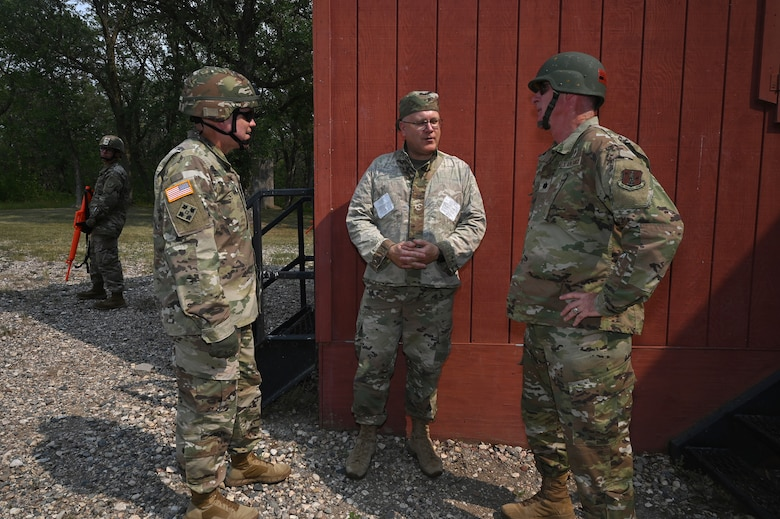 Three North Dakota National Guard chaplains in military uniform simulate discussions as if meeting in a foreign land during training at Camp Grafton Training Center, N.D., Aug. 3, 2021.
