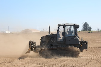 """PORT HUENEME, Calif. (Aug. 26, 2021) Rear Adm. Peter Garvin trains to drive the D5 dozer at the equipment operator schoolhouse """"Dozer Field"""" at Naval Construction Training Center (NCTC)  Port Hueneme.  NCTC Port Hueneme is one of five learning sites in the Center for Seabees and Facilities Engineering domain.  They train and develop Sailors, Soldiers, Airmen, and Marines in construction trades to accomplish contingency and peacetime construction, chemical, biological, and radiological operations, and humanitarian assistance missions worldwide. (U.S. Navy photo by Amber Vaglica)"""