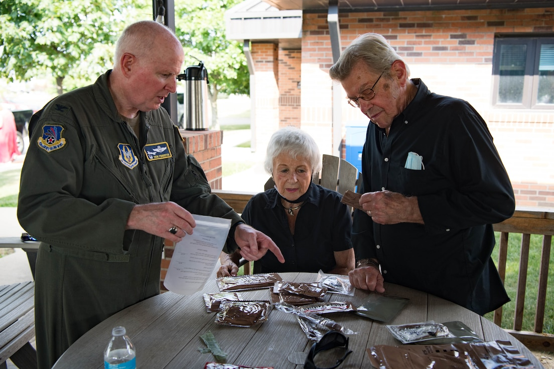 Col. Thom Pemberton, 434th Air Refueling Wing commander, goes over the finer points of cooking an MRE to Phil and Joan Lake during a Grissom Community Council outing Aug. 20, 2021. The GCC members visited the base, watched as unit members responded to a wartime scenario before dining at Chocks. (U.S. Air Force photo/Staff Sgt. Jeremy Blocker)