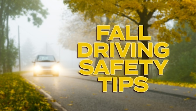 Car driving in the fall season with headlights on.