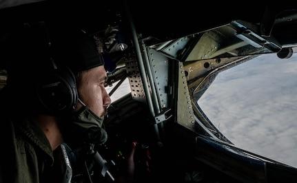 An Airman prepares to refuel a jet mid-air.