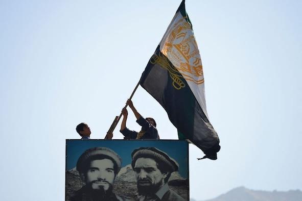 Afghan men wave a flag above the portrait of late Afghan commander Ahmad Shah Massoud