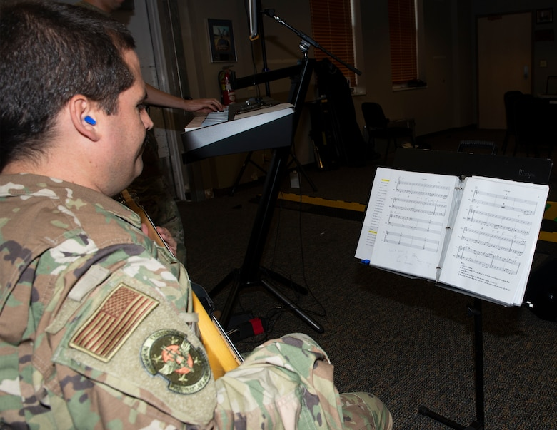 airmen in uniform sitting holding bass guitar with sheet music on a stand