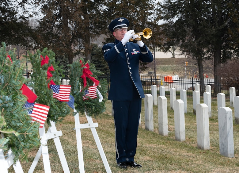 airmen in uniform standing in the middle of wreaths on easels and the first row of headstones at a cemetery