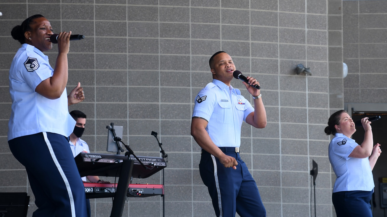 three airmen in uniform holding microphones and singing