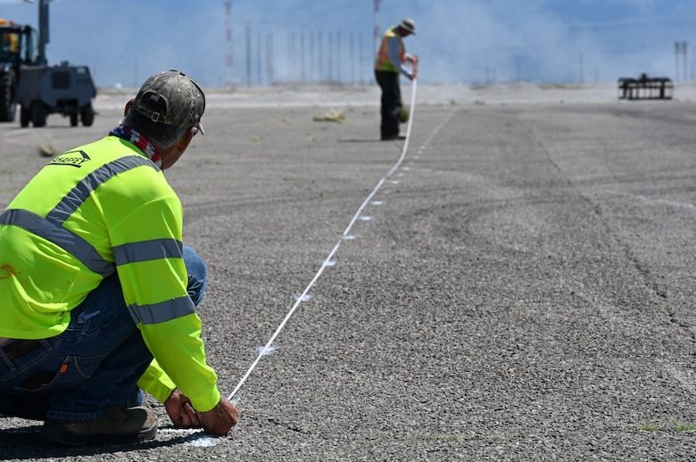 Two contractors prepare guide lines at a future Afghan personnel housing facility construction site in support of Operation Allies Welcome, Aug. 27, 2021, on Holloman Air Force Base, New Mexico. The Department of Defense, through U.S. Northern Command, and in support of the Department of Homeland Security, is providing transportation, temporary housing, medical screening, and general support for up to 50,000 Afghan evacuees at suitable facilities, in permanent or temporary structures, as quickly as possible. This initiative provides Afghan personnel essential support at secure locations outside Afghanistan. (U.S. Air Force photo by Staff Sgt. Christopher S. Sparks)