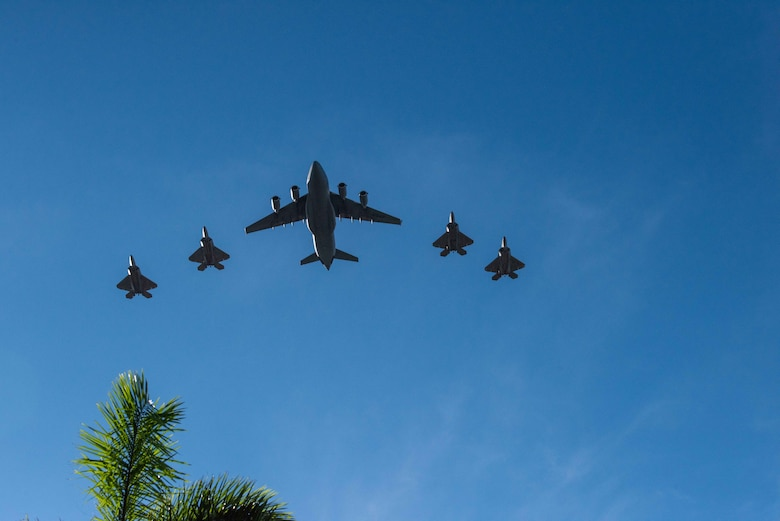Photo of Four Hawaii F-22 Raptors and a C-17 Globemaster III from the 535th Airlift Squadron conducting a flyover.