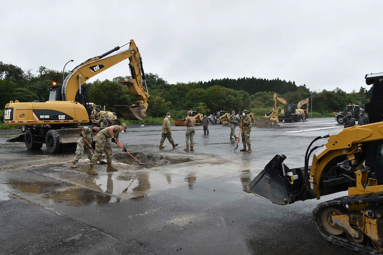 In a rapid airfield damage repair site two military members scrape rumble into a hole.
