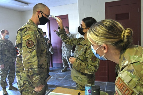 Oregon National Guard Tech. Sgt. Meghan Olson, 173rd Medical Group, checks the temperature of Senior Master Sgt. John Wyman, 270th Air Traffic Control Squadron, while Capt. Jaimie Nealy reviews his paperwork during an inprocessing briefing for Airmen activated to support hospitals across Oregon Sept. 2, 2021, at Kingsley Field in Klamath Falls, Oregon.