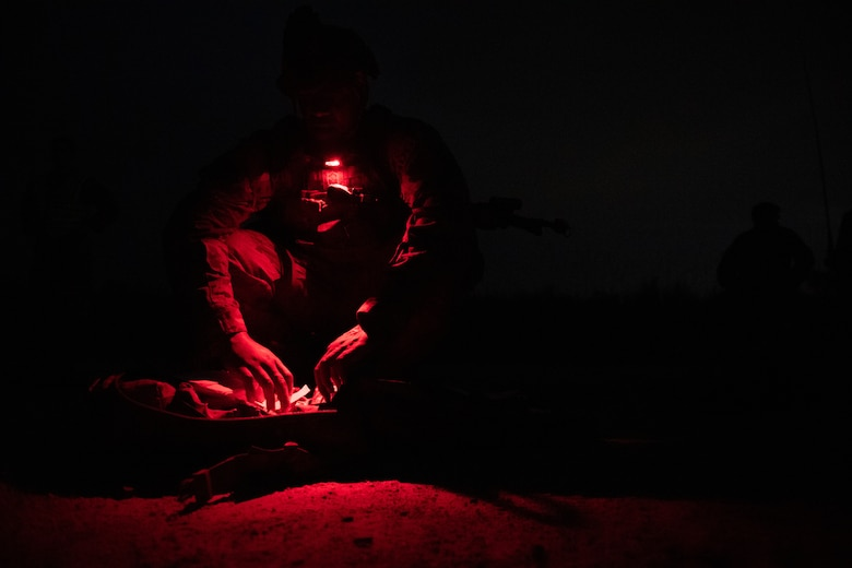 Photo of Airmen looking into a bag at night
