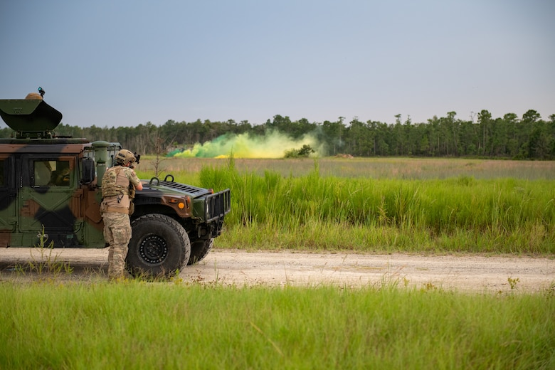 Photo of Airman with a rifle in front of a Humvee