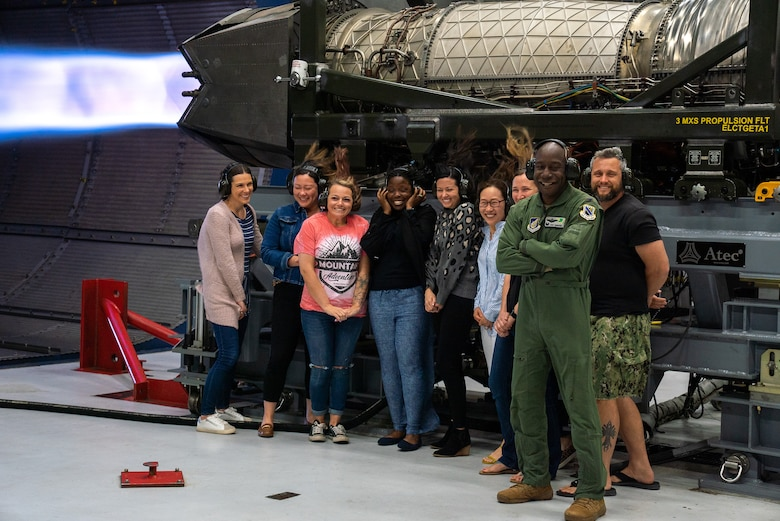 U.S. Air Force Col. Travolis Simmons, the 3rd Wing commander, stands with 3rd Wing spouses next to a running F-22 Raptor engine during an immersion tour on Joint Base Elmendorf-Richardson, Alaska.