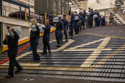 Sailors walk food and water down to a landing craft, utility (LCU), in Arlington's well deck prior to delivering humanitarian aid to the Port of J�r�mie, Haiti, Aug. 31, 2021.