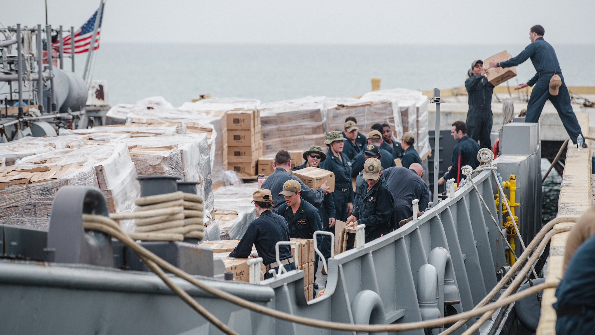 U.S. Marines and Sailors with Joint Task Force-Haiti (JTF-Haiti) and volunteers help offload boxes for redistribution in Port of Jeremie, Haiti.