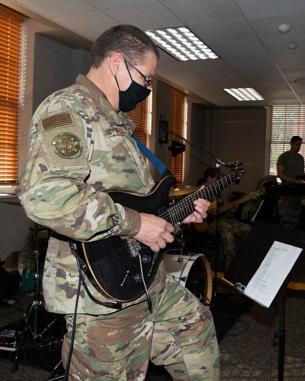 airman in uniform playing his guitar