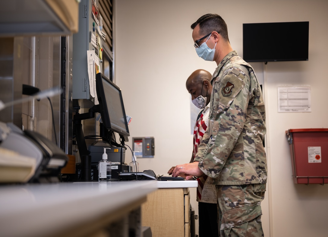 U.S. Air Force Tech. Sgt. Andrew Bañales, 18th Medical Support Squadron NCO in charge of pharmacy, checks in a patient at Kadena Air Base, Japan, Sept. 1, 2021. The 18th MDSS serves as the lead agent for medical material in the Indo-Pacific region. (U.S. Air Force photo by Airman 1st Class Stephen Pulter)