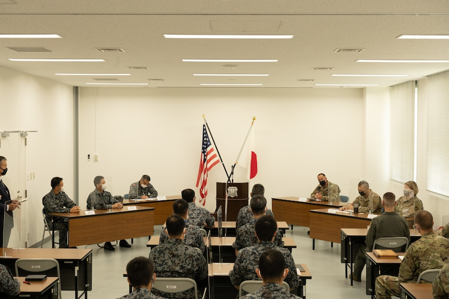 Several people in uniform are seated in a large room. At the front of the room are the American and Japanese flags.
