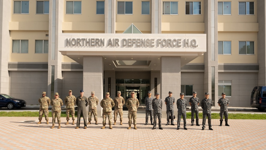Several uniformed people stand in formation in front of a building that reads: Northern Air Defense Force H.Q.