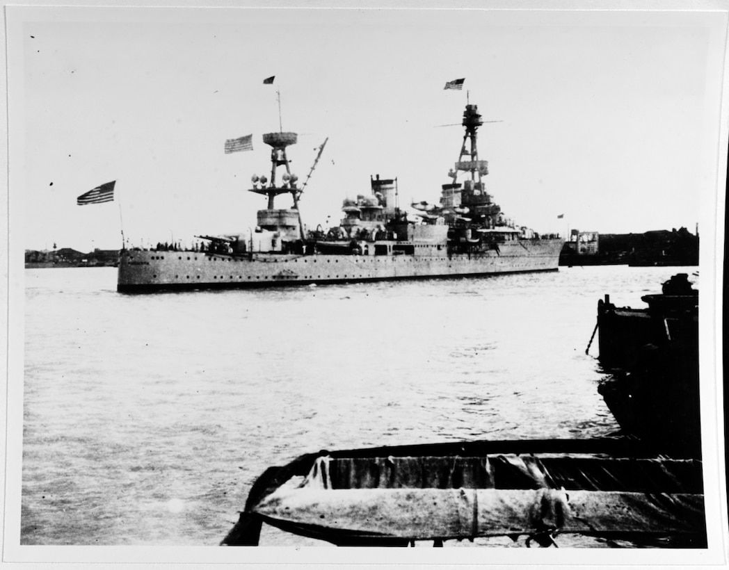 """USS Augusta (CA-31). View taken off the """"Bund"""" at Shanghai, China, being moved into position at the foot of """"Man of War"""" row, during the Sino-Japanese hostilities there, 18 August 1937. Note American flags at fore, gaff, and flagstaff. Ship was then the flagship of Admiral H.E. Yarnell, USN, CINCAF (NH 84774)."""