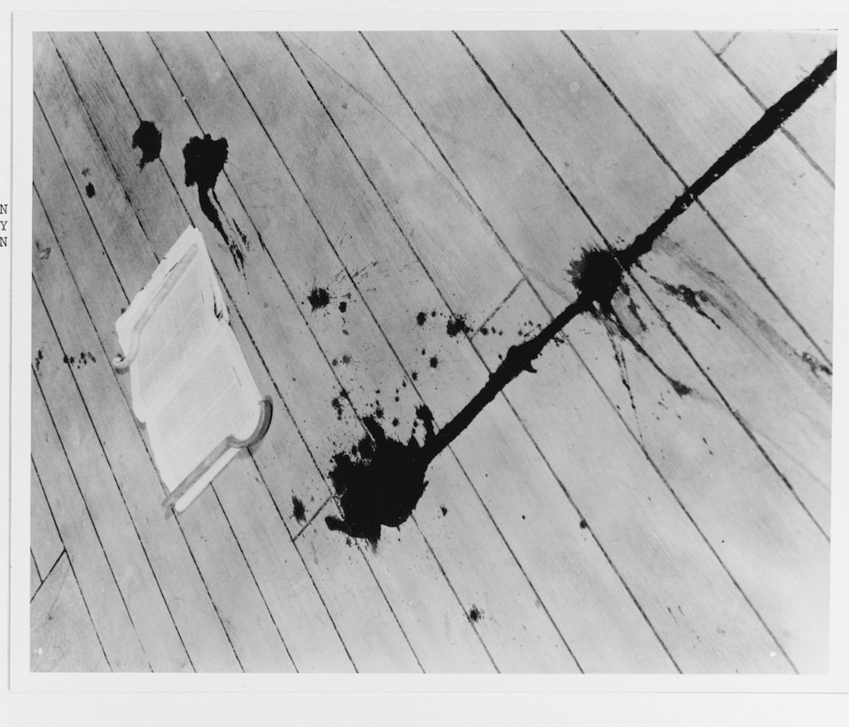 Trail of blood on the deck of USS Augusta from Seaman First Class Freddie J. Falgout, killed by splinters from an antiaircraft shell on 20 August 1937. The magazine that Falgout was reading while waiting for the movies to begin lies on the deck (NH 77831).