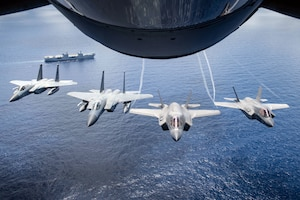 Two U.S. Marine Attack Squadron 211 F-35B Lightning IIs and two U.S. Air Force F-15 Eagles assigned to the 67th Fighter Squadron, fly over United Kingdom aircraft carrier HMS Queen Elizabeth over the west Indo-Pacific region
