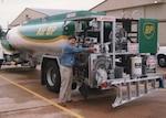 a man stands next to a fuel truck