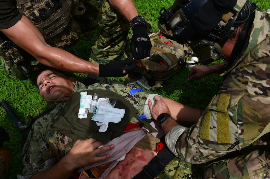 U.S. Naval Special Warfare (NSW) operators start an IV for a simulated wounded service member during an urban combat training scenario as part of MALABAR 2021.