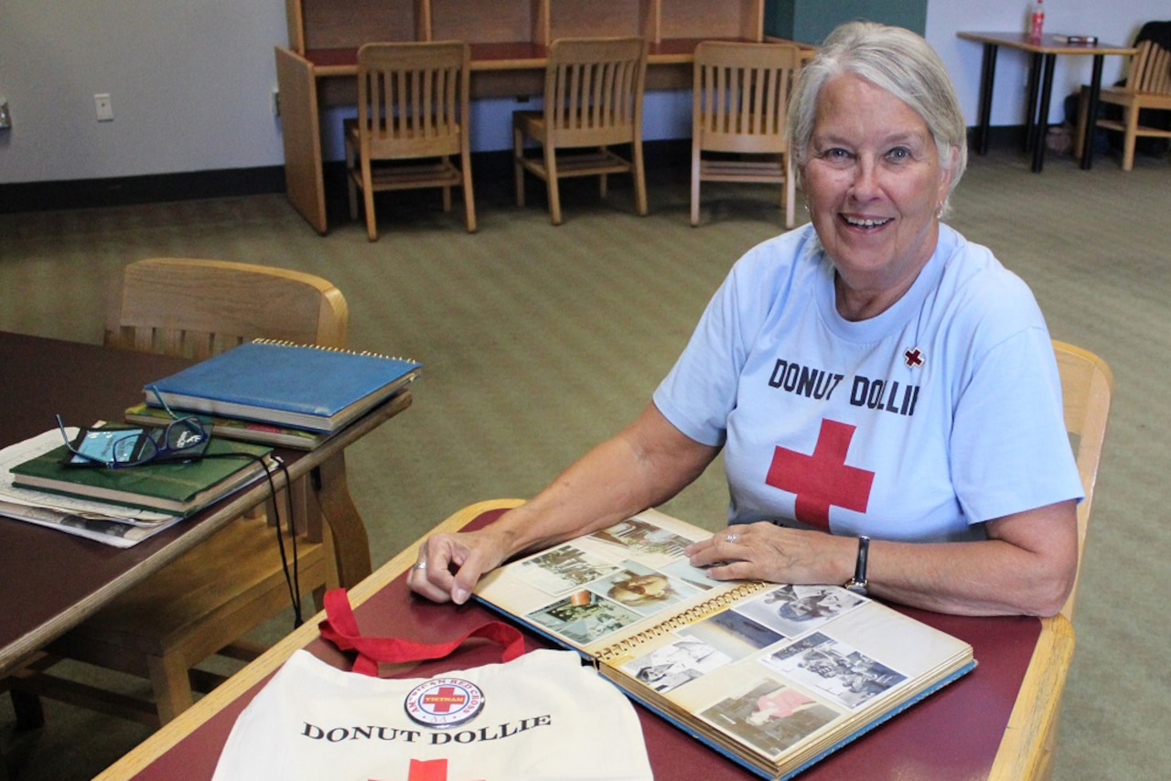 woman smiles while sitting at a table with an open scrapbook.