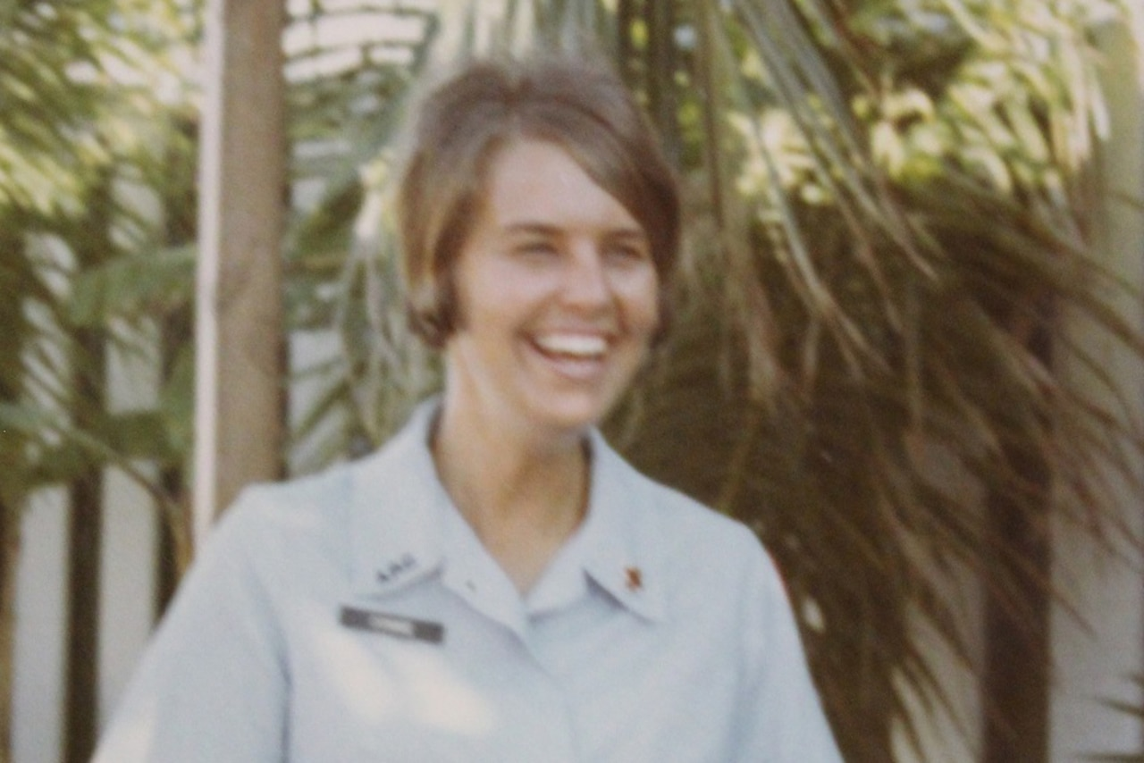 Woman smiles outside in front of tropical foliage.