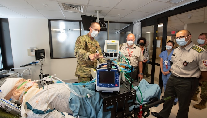 Maj. (Dr.) Andrew Bergland, 88th Medical Group, briefs Serbian Col. (Dr.) Danilo Jokovic (center) and Lt. Col. (Dr.) Vladan Zivkovic on the system Wright-Patterson Medical Center's Intensive Care Unit uses to transport COVID-19 patients. The doctors leda Serbian delegation sponsored by the Ohio National Guard's State Partnership Program.