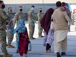 Afghan evacuees arrive in Indianapolis Sept. 2, 2021, as 1st Cavalry Division Soldiers watch. Hoosiers will host the Afghans at Camp Atterbury, near Edinburgh, as they begin their safe resettlement to the United States. The division Soldiers along with Indiana National Guard Soldiers will provide transportation, temporary housing, medical screening and logistics support as part of Operation Allies Welcome.