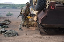 A photo of a pararescueman opening an overturned vehicle with a saw.