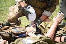 A photo of a pararescueman operating on a simulated injured victim.
