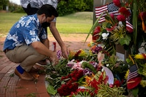 Patrick Pihana Branco, Hawaii state representative, arranges floral bouquets brought by local community members at the Pacific War Memorial during a ceremony held in remembrance of the fallen aboard MCBH, Aug. 29, 2021. In support of the 13 service members who lost their lives in Afghanistan, members of the community brought flowers to later be placed at the Pacific War Memorial for a small, private ceremony. (U.S. Marine Corps photo by Gunnery Sgt. Orlando Perez)