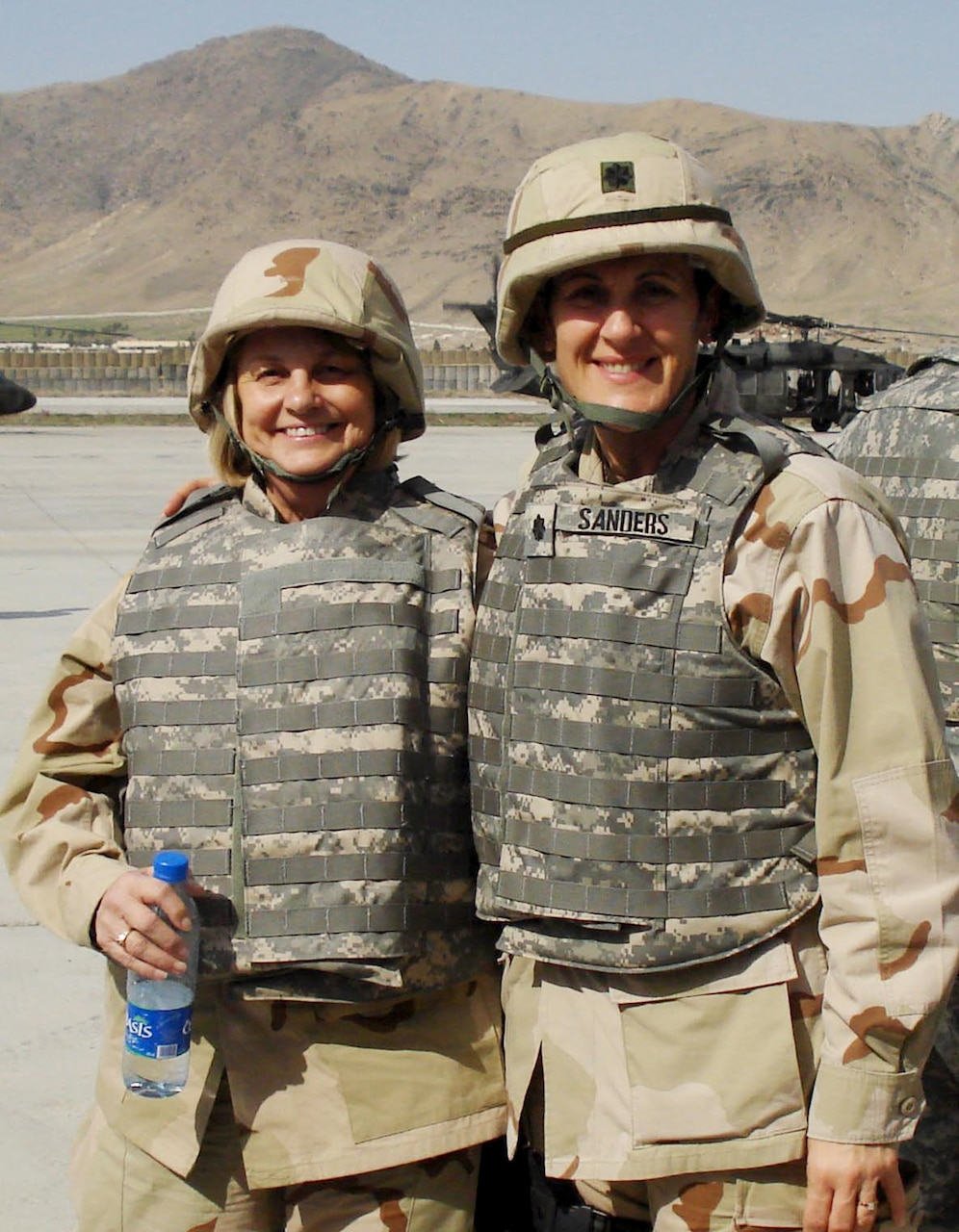 Two women in flak vests and hard hats stand on the tarmac.