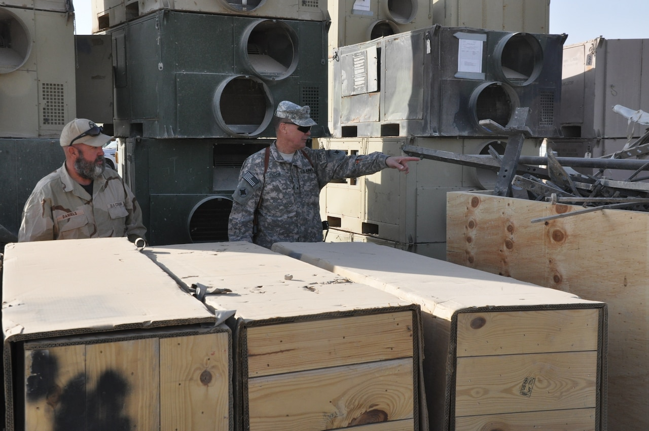 Two men, one in uniform, stand amidst crates of supplies.