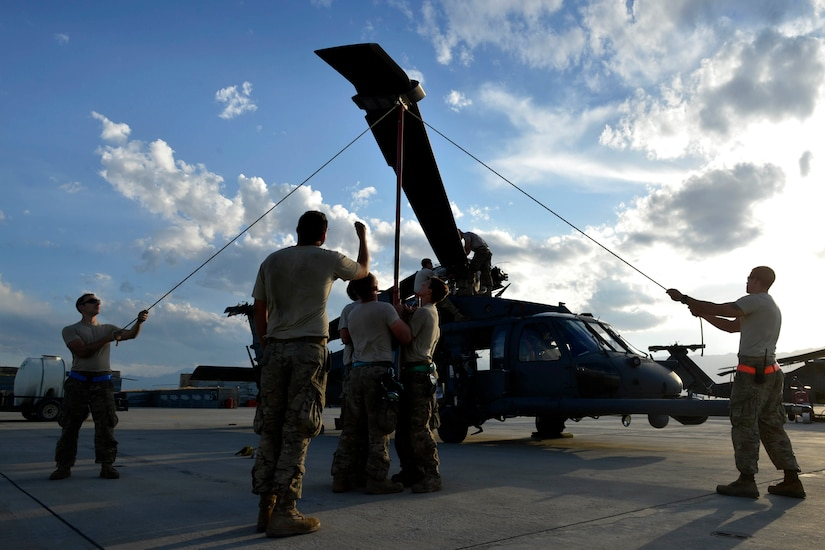 Airman perform maintenance on a helicopter.