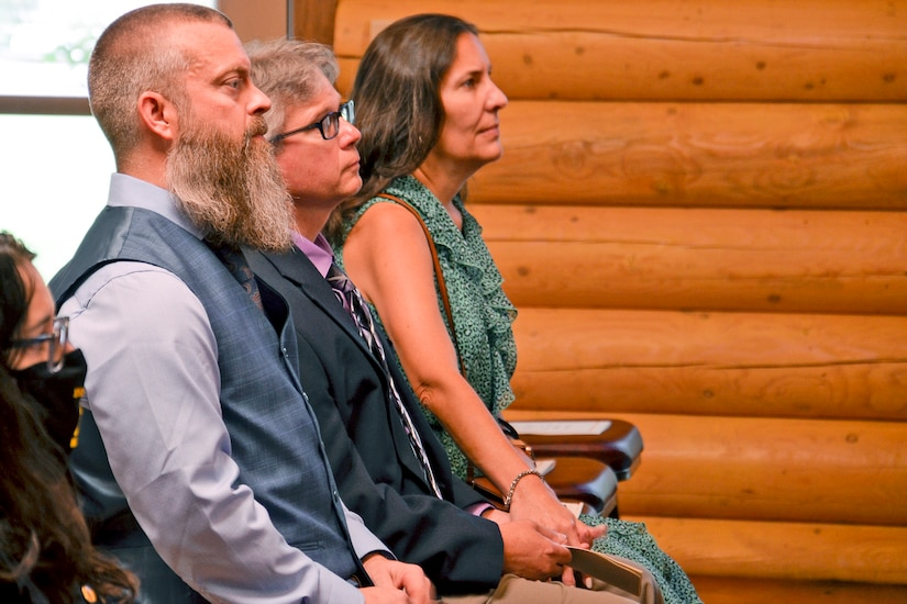 Two women and a man attend a service.
