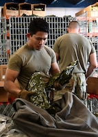 Senior Airman Rithy Panha Von Chhay, 102nd Logistics Readiness Squadron material manager, assists the 104 LRS with processing mobility bags during a mobility exercise August 13, 2021, at Barnes Air National Guard Base, Massachusetts. The exercise was in progress August 9-15 and served as a practice opportunity for members to evaluate capabilities of their squadrons in the event of a base-wide mobilization. (U.S. Air National Guard photo by Staff Sgt. Sara Kolinski)