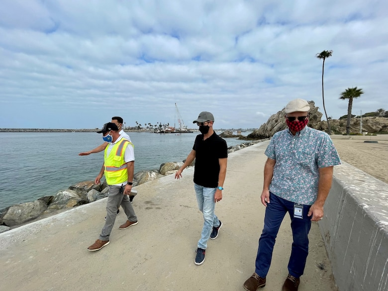 Mark Golay, second from right, U.S. Army Corps of Engineers Los Angeles District Navigation Branch program manager, accompanies Chris Miller, right, public works manager with the City of Newport Beach; Robert Silva, left-foreground, construction inspection supervisor with the City of Newport Beach; and Jorge Tomas, director of operations and sales with Pacific Dredge, on a walkthrough of the Newport Bay Harbor east jetty Sept. 1, 2021, in Newport Beach, California.