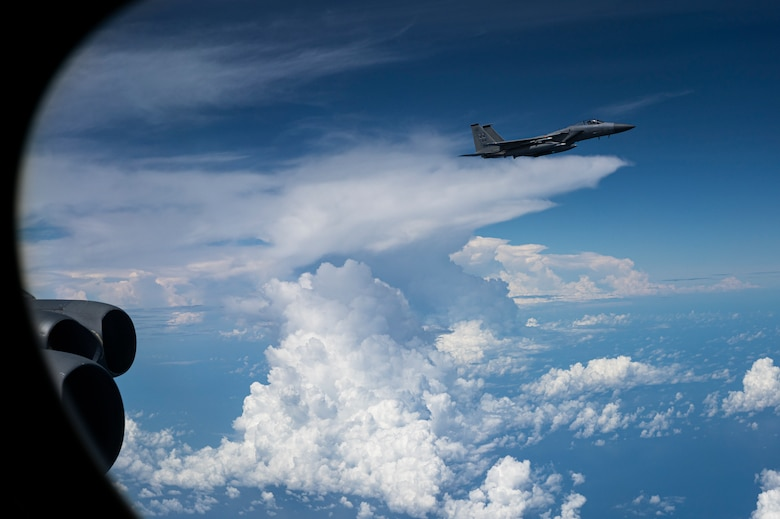 A U.S. Air Force F-15C Eagle, assigned to the 18th Wing, Kadena Air Base, Japan, escorts a U.S. Air Force B-52H Stratofortress, assigned to the 2nd Bomb Wing, Barksdale Air Force Base, Louisiana, during a Bomber Task Force (BTF) mission over the Indo-Pacific region, Sep. 5, 2021. The B-52 is a long-range bomber with a range of approximately 8,800 miles, enabling rapid support of BTF missions or deployments and reinforcing global security and stability. (U.S. Air Force photo by Staff Sgt. Devin M. Rumbaugh)
