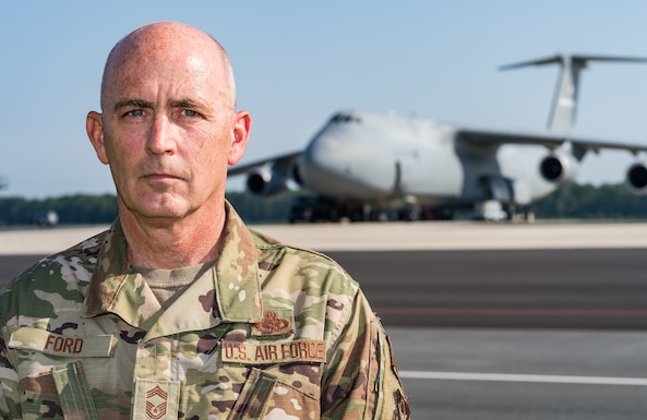 """Chief Master Sgt. Bryan """"Skip"""" Ford, 512th Aircraft Maintenance Squadron superintendent, poses for a photo near the flight line near a C-5M Super Galaxy on Dover Air Force Base, Delaware, Aug. 25, 2021. Ford recently recalled the events of Sept. 11, 2001, while stationed at Dover AFB and how 9/11 changed how he viewed our relative security and freedom as a nation. (U.S. Air Force photo by Roland Balik)"""