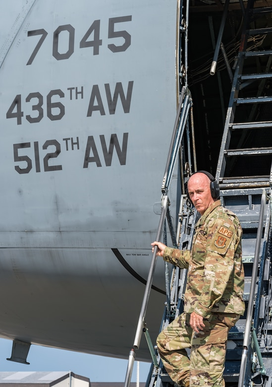 """Chief Master Sgt. Bryan """"Skip"""" Ford, 512th Aircraft Maintenance Squadron superintendent, poses for a photo on the crew entrance ladder of a C-5M Super Galaxy at Dover Air Force Base, Delaware, Aug. 25, 2021. Ford recently recalled the events of Sept. 11, 2001, while stationed at Dover AFB and how 9/11 changed how he viewed our relative security and freedom as a nation. (U.S. Air Force photo by Roland Balik)"""