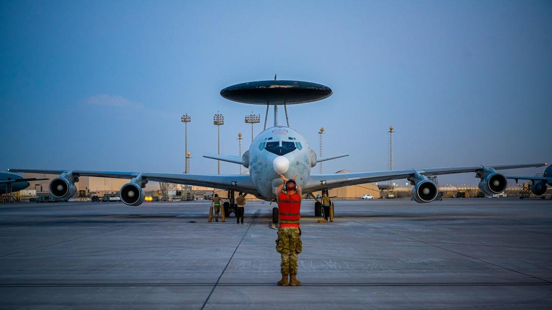 Airman signaling an E-3 Sentry aircraft into parking spot