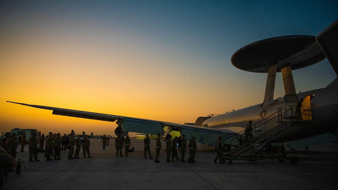 Airmen celebrate next to an E-3 Sentry aircraft