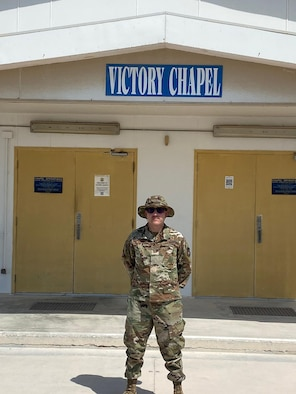 Airman stands in front of chapel