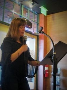 Diane Guarnieri, published poet and Defense Logistics Agency Troop Support employee, performs a poem aloud with a microphone while standing at a podium.
